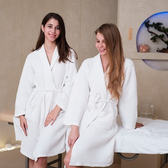 Friends posing in bath robes at spa