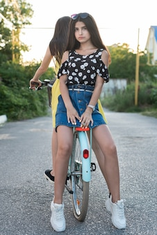 Friends posing together on bicycle