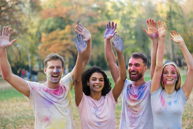 Friends posing while holding colored hands in the air