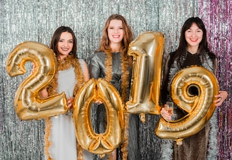 Friends posing with golden balloons at a new year party