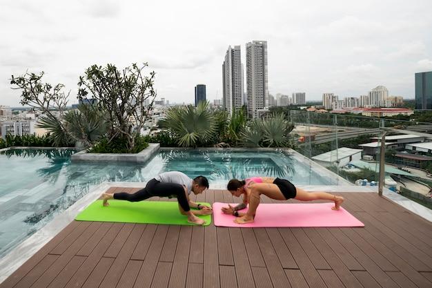 Друзья вместе практикуют йогу на открытом воздухе