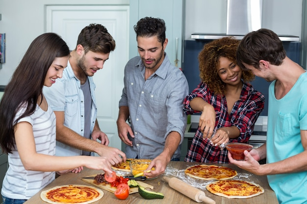 Friends preparing pizza on kitchen table