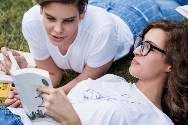Друзья читают книги, лежащие на траве