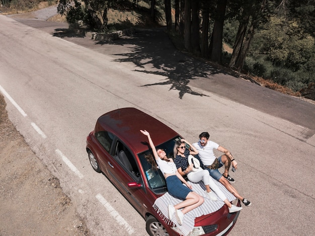 Friends relaxing on car hood over the road