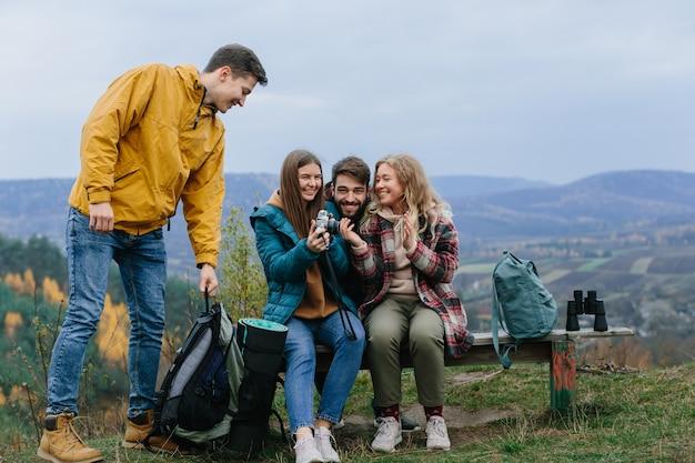 Друзья отдыхают на скамейке в горах во время восхождения