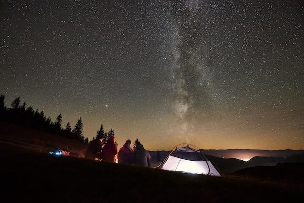 Friends resting beside camp, campfire under night starry sky