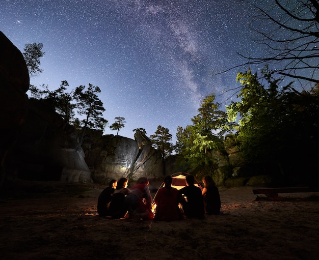 夜にキャンプファイヤーの横で休んでいる友達