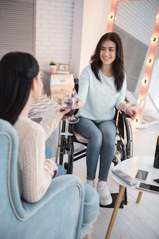 Воссоединение друзей. радостная женщина-инвалид, наслаждаясь вином и разговаривая с другом