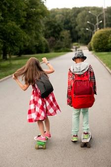 Amici che guidano skateboard nel parco