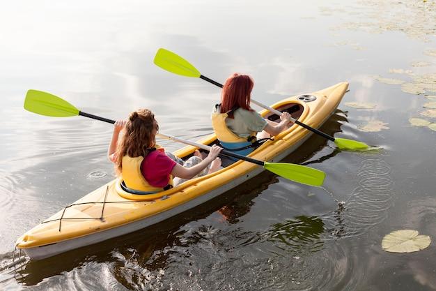 Friends rowing in kayak on lake