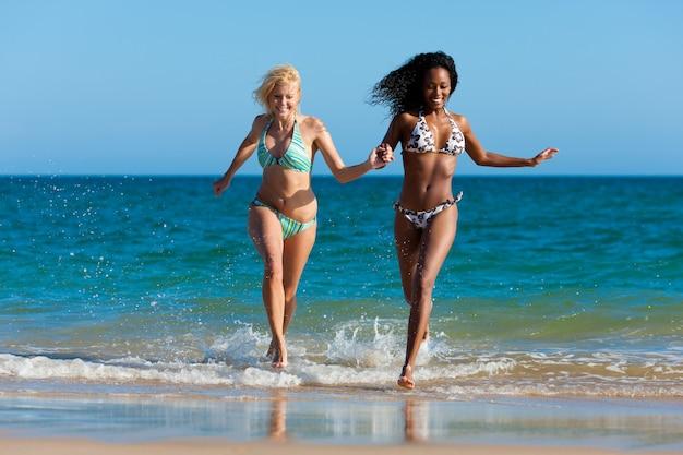 Friends running on beach vacation