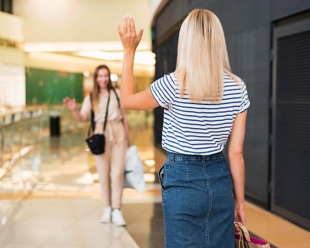 ショッピングモールでお互いに敬礼する友人