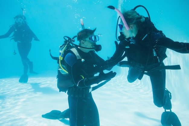 Friends on scuba training submerged in swimming pool