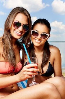 Friends sharing a drink on the beach