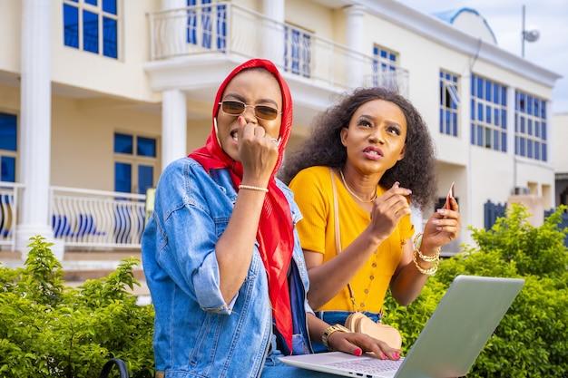 Amici che fanno acquisti online seduti in un parco