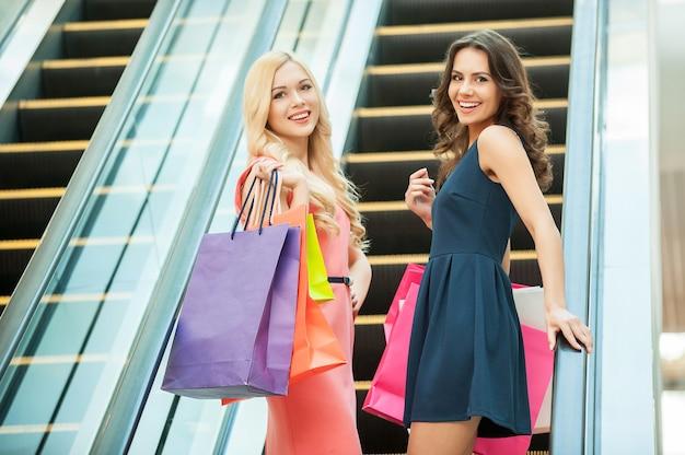 Друзья по магазинам. две красивые молодые женщины на эскалаторе в торговом центре
