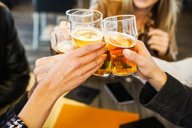 Friends showing hands while holding glasses of beer and cheering with each other