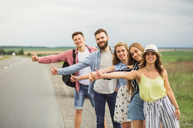 Friends showing thumbs up on street for hitchhiking during road trip