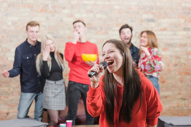 Friends singing karaoke at a party
