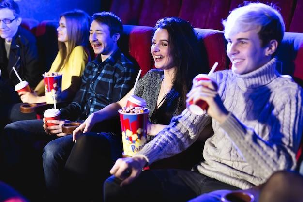 Друзья вместе сидят и едят попкорн во время просмотра фильмов в кинотеатре