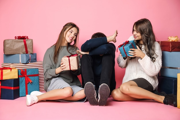 Friends sitting among christmas gifts on pink