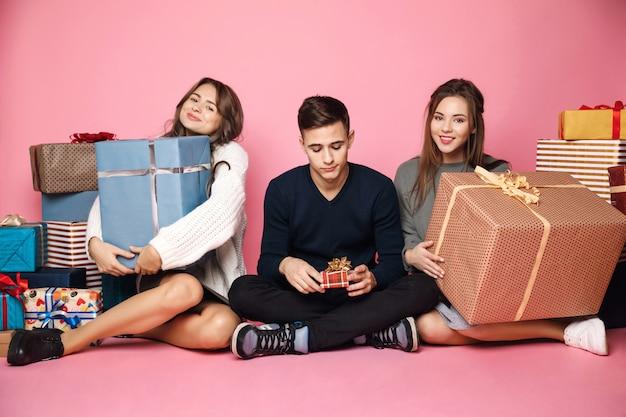 Друзья сидят среди рождественских подарков. женщины держат большие коробки, парень маленький.