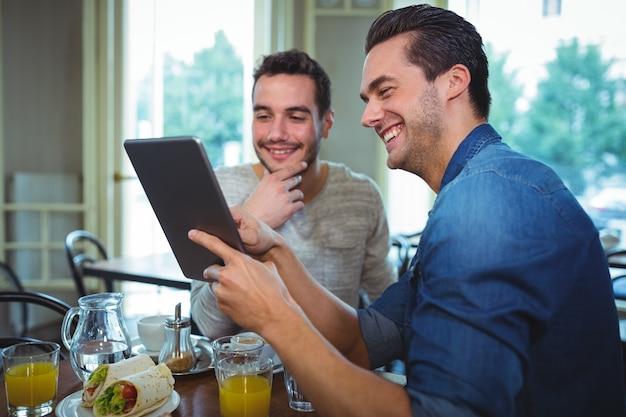 Друзья, сидя за столом и с помощью цифрового планшета в кафе
