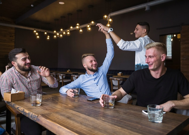 Friends sitting in the bar giving high five
