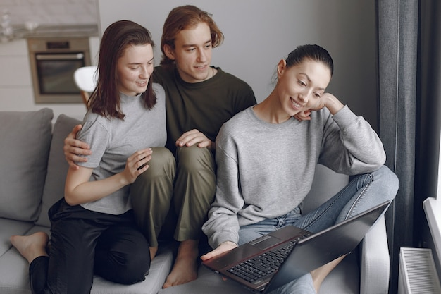 Friends sitting on a bed in a room and use a laptop