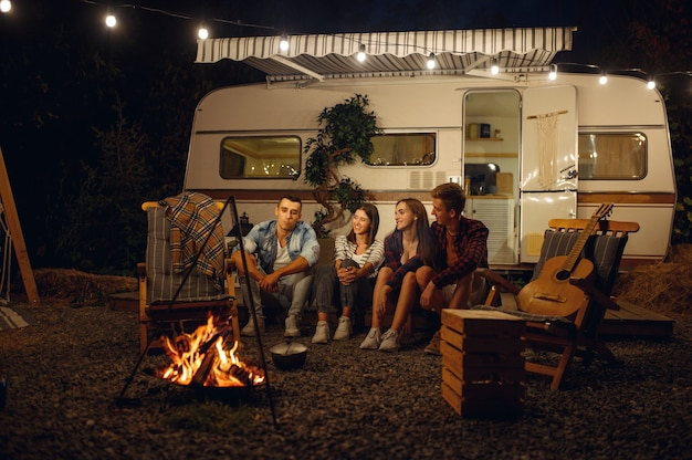 Friends sitting by the campfire in the night, picnic at camping in the forest