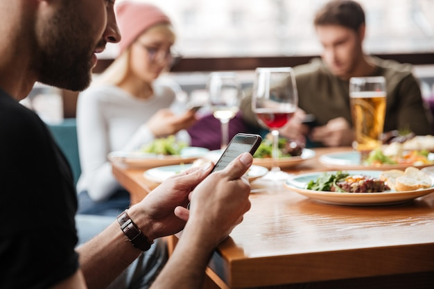 Friends sitting in cafe and using mobile phones