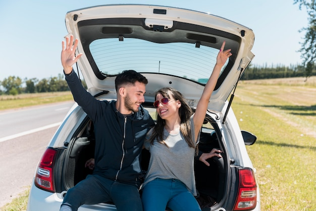 Friends sitting on car trunk making peace sign