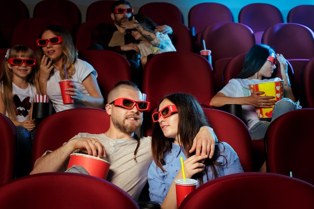 Friends sitting in cinema watch film eating popcorn and drinking water.