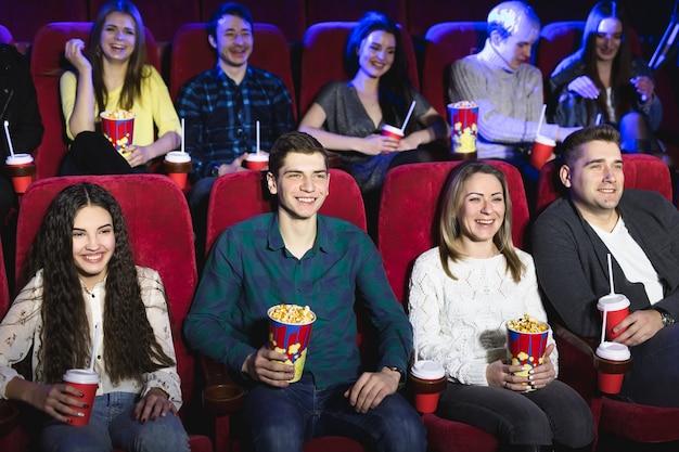 Friends sitting in a cinema watch film eating popcorn