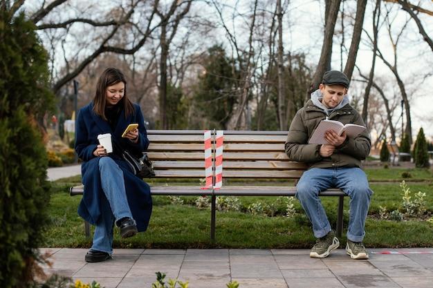 Amici seduti a distanza e con indosso una maschera