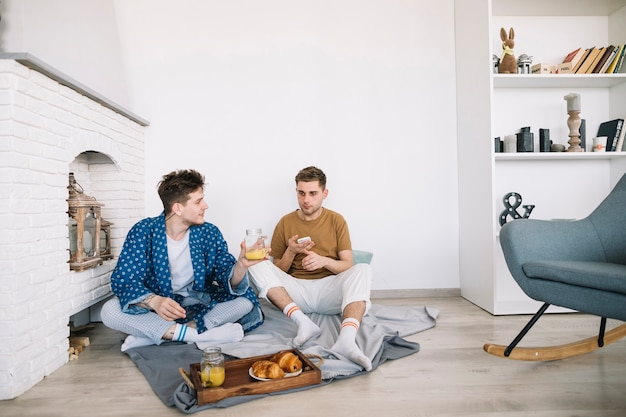Friends sitting on floor having delicious food at home