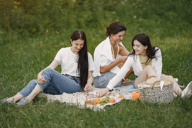 Friends sitting on a grass. girls on a blanket. woman in a white shirt.