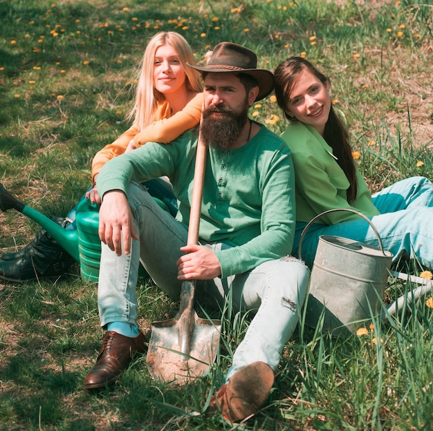 Friends sitting on grass at spring garden. portrait of caucasian male farmer with shovel with two friend girl. relaxing after hard work.