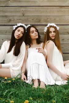 Friends sitting in the grass with flower diadem