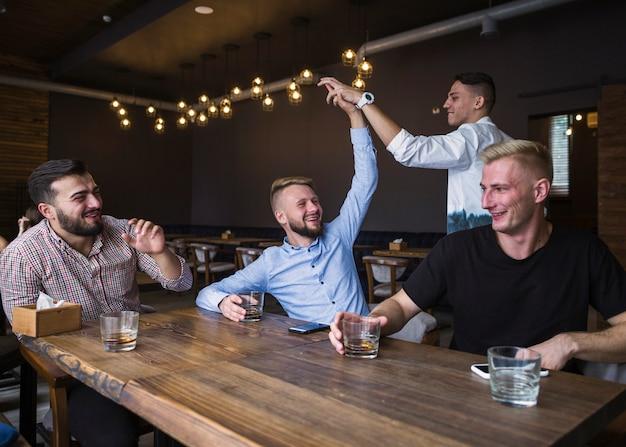 Друзья сидят в баре, давая пять