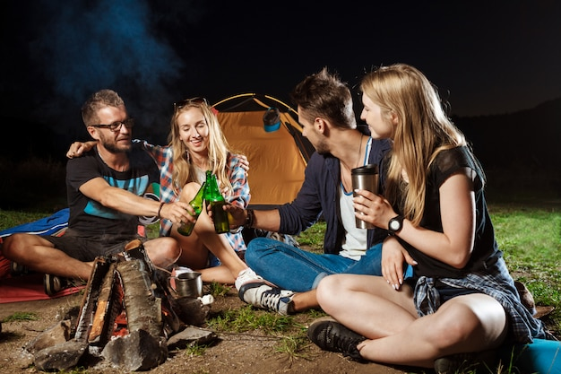 Friends sitting near bonfire, smiling, speaking, resting, drinking bear