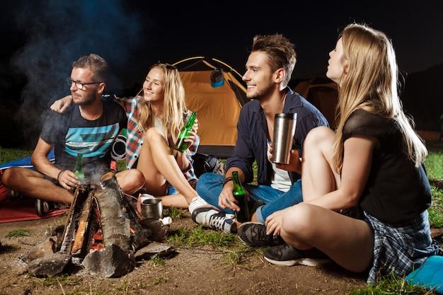 모닥불 근처에 앉아 웃 고, 말하기, 휴식, 곰 마시는 친구