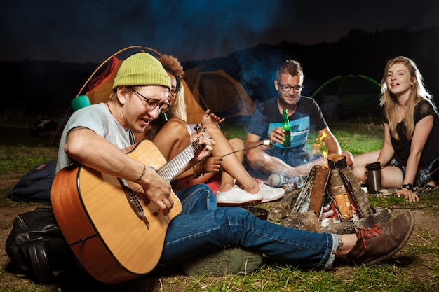 Friends sitting near bonfire, smiling, speaking, resting, playing guitar