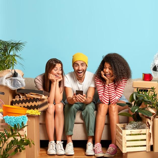 Друзья сидят на диване в окружении коробок