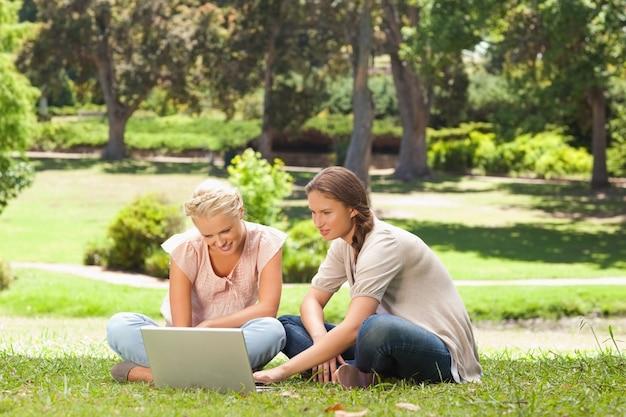 ラップトップで芝生に座っている友達
