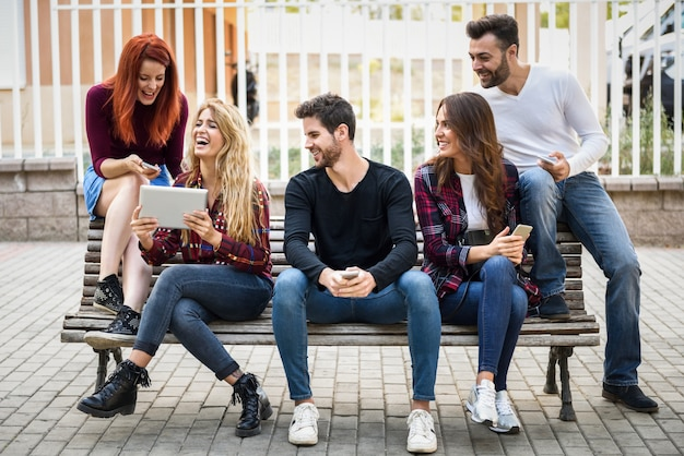 Friends sitting on a wooden bench in the street and looking at a tablet of a girl