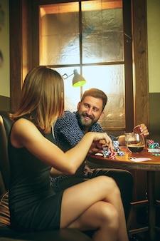 Amici seduti al tavolo di legno. amici che si divertono durante il gioco da tavolo.