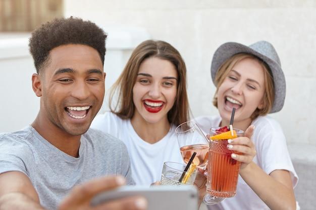 Selfieを取っている間携帯電話のカメラに笑顔の友人