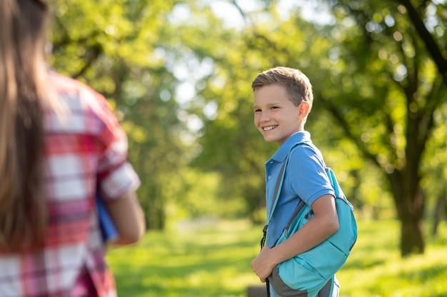 Друзья. улыбающийся мальчик в синей футболке с рюкзаком и девочка, стоящая спиной к камере на открытом воздухе в прекрасный день Premium Фотографии
