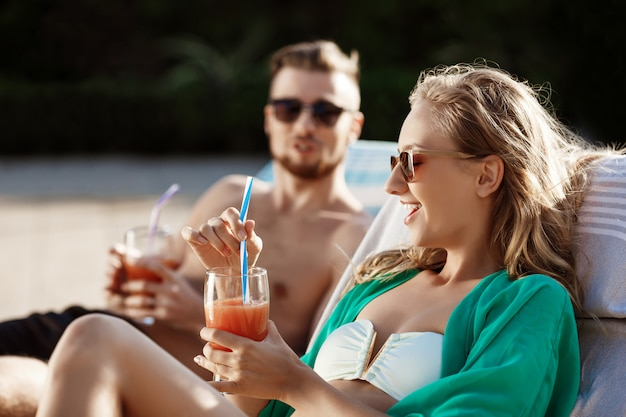 Friends smiling, drinking cocktails, lying on chaises near swimming pool